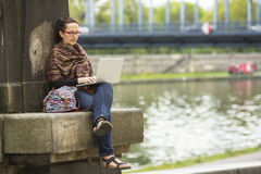 Woman with laptop sitting outdoors in an old European city. Stock Images