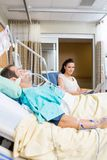 Woman With Laptop Sitting By Patient In Hospital Stock Photos