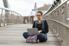 Woman with laptop sitting on a pedestrian bridge in an old European city. Royalty Free Stock Image