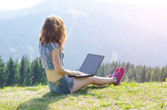 Woman with laptop sitting on top of a mountain, free space for y Royalty Free Stock Images