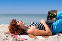 Woman with laptop sleep at sea coast Stock Photo