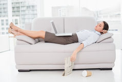 Woman with laptop sleeping on sofa at home Stock Photos