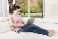 Woman with laptop and smartphone on couch Royalty Free Stock Images