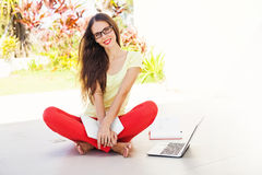 Woman with laptop. Smiling woman sitting in the porch with laptop and notebooks Stock Photography