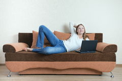 Woman with laptop on the sofa Royalty Free Stock Images