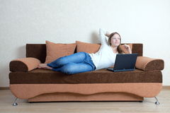 Woman with laptop on the sofa Royalty Free Stock Image