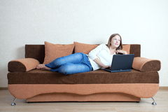Woman with laptop on the sofa Stock Photos