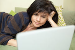 Woman with laptop on sofa Stock Photography