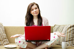 Woman with a laptop on a sofa working Stock Photos