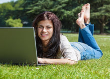 Woman with laptop in summer park. Young brunette woman with laptop computer lying  on grass in a park Stock Photo
