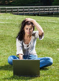 Woman with laptop in summer park. Young brunette woman with laptop computer sitting on grass in a park Royalty Free Stock Photography