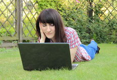 Woman with laptop in the sunny garden Stock Photo