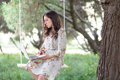 Woman with Laptop on a Swing Royalty Free Stock Photo