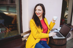 Woman with laptop and tea outdoors in cafe Stock Photography