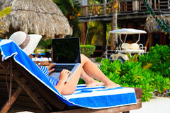 Woman with laptop on tropical beach Royalty Free Stock Photo