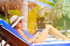 Woman with laptop on tropical beach Stock Images