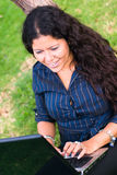 Woman laptop typing. Lady latina with laptop outdoors Royalty Free Stock Images