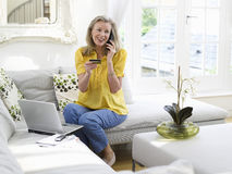 Woman With Laptop Using Credit Card And Phone Stock Images