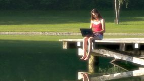 Woman with laptop on vacation on the lake stock video