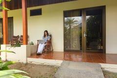 Woman with laptop on veranda Stock Photo