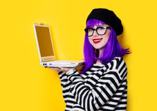 Woman with laptop. Violet hair woman with laptop on yellow background Royalty Free Stock Image