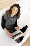 Woman with laptop on white sheet in her bed at home Stock Image