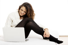 Woman with laptop on white sheet in her bed at home Royalty Free Stock Photos