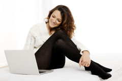 Woman with laptop on white sheet in her bed at home Royalty Free Stock Photography