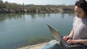 Woman with laptop working by the river. Girl is typing on a laptop in the fresh air. stock video