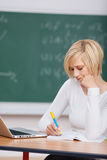 Woman With Laptop Writing Notes At Desk Royalty Free Stock Photography