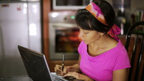 Woman with laptop writing recipe from internet in kitchen stock video