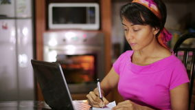 Woman with laptop writing recipe from internet in kitchen stock video footage