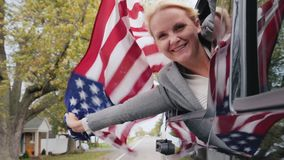 A woman with a large American flag looks out of the window of a traveling car. Slow motion video. A woman with a dog and an American flag looks out of the car stock footage