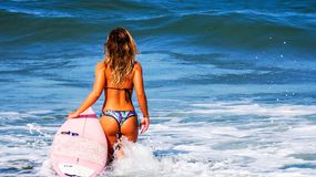 Woman on Large Body of Water during Daytime Holding Surf Board Stock Photos