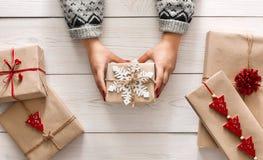 Woman& x27; las manos de s muestran el día de fiesta de la Navidad presente con guita del arte Fotografía de archivo libre de regalías
