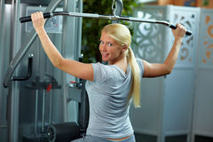 Woman at lat machine. Woman doing exercises on a lat machine in a gym royalty free stock photo
