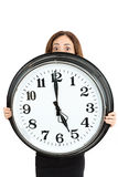 Woman late and showing the time with shocked eyes. Woman showing big clock and has a panicked expression because she is late for appointment. Isolated on white Stock Image