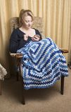 Woman in late twenties relaxing at home. With blanket and playing on her phone Stock Photography