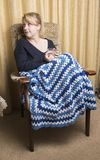 Woman in late twenties relaxing at home. With blanket and a cup of hot chocolate Royalty Free Stock Photo