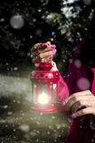 Woman with latern. Woman hand with latern. Christmas background with snow in outdoor Royalty Free Stock Images