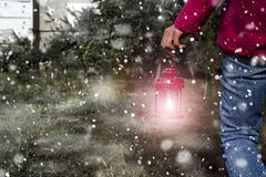 Woman with latern. Woman hand with latern. Christmas background with snow in outdoor Royalty Free Stock Photo