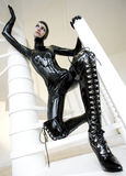 Woman in latex. Sitting on the stairs Royalty Free Stock Photos