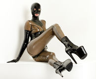Woman in latex. Sitting woman wearing latex clothes Royalty Free Stock Photography