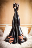 Woman in latex in bed. Young woman on diets thumb up Royalty Free Stock Images