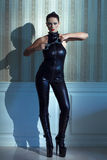 Woman in latex catsuit holding handcuffs Royalty Free Stock Image