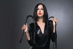 Woman in latex suit on a dark background. Beautiful woman in latex suit with whip on a dark background stock photography