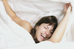Woman laugh in feather bed. Woman awakes with a beautyful smile in white feather bed under the white coverlet bedspread Stock Image