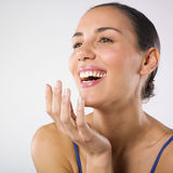 Woman laughing. A studio portrait of a beautiful young woman laughing. Wellness concept Stock Images