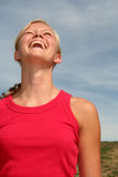 Woman laughing against blue sky Royalty Free Stock Images