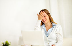 Woman laughing alone while is using on laptop Stock Images